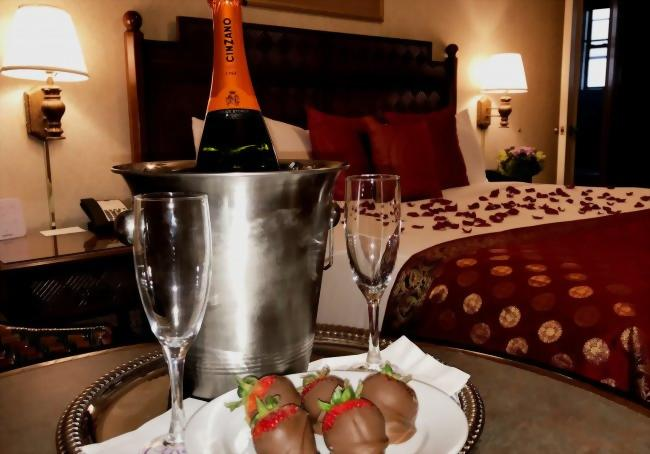 A bottle of chilled prosecco, chocolate covered strawberries, and bed with rose pedals.