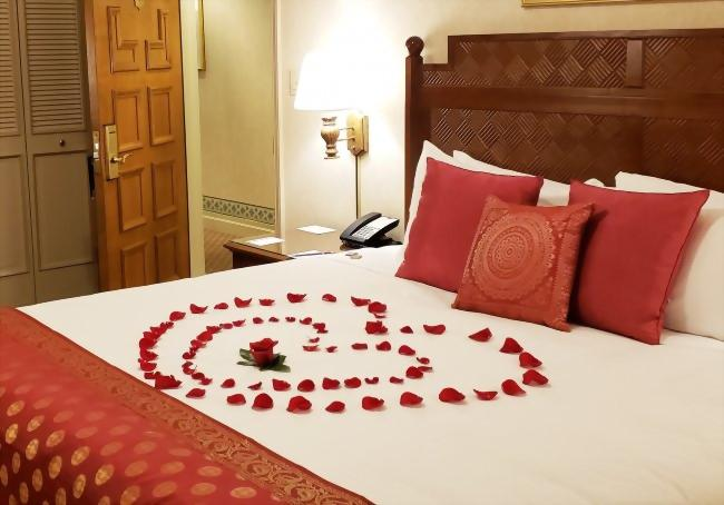Bed set up with rose petal turndown service.
